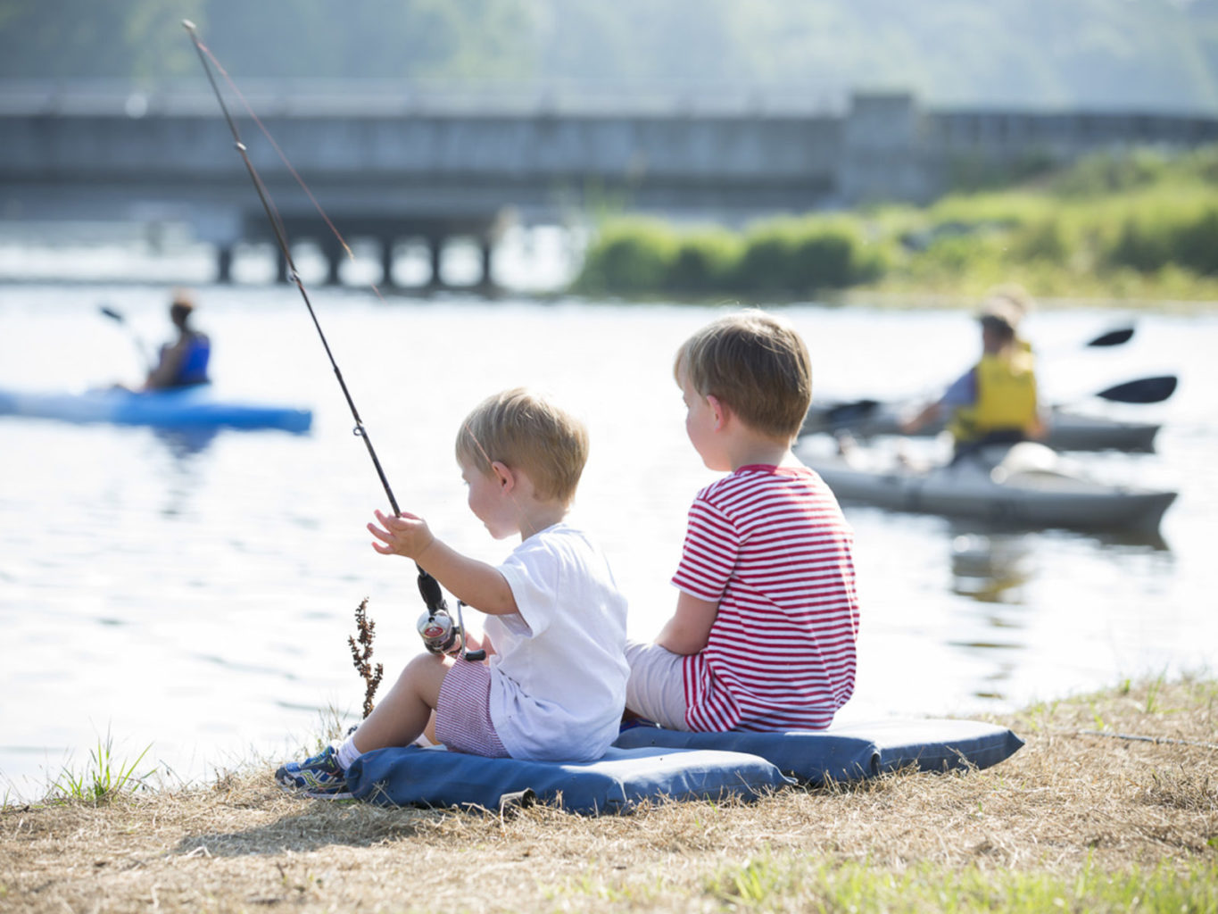 Kids fishing in Lake Blackshear while a family kayaks by the SAM Trainline